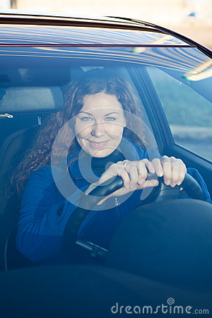 Woman looking through the car windshield glass
