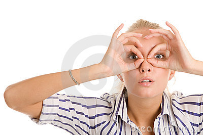 Woman looking through circled fingers Stock Photo