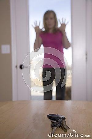 Woman looking through door at keys