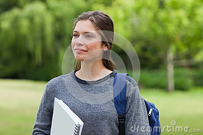 Woman looking far away while standing in a park wi