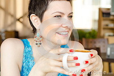 Woman looking forward, as she holds a mug
