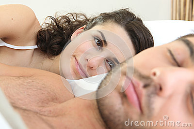 Woman looking at her husband sleep