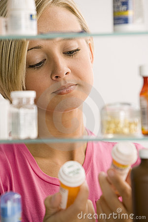 Free Woman Looking In Medicine Cabinet Stock Photo - 14645620