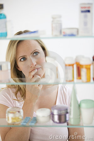 Free Woman Looking In Medicine Cabinet Royalty Free Stock Image - 14646706