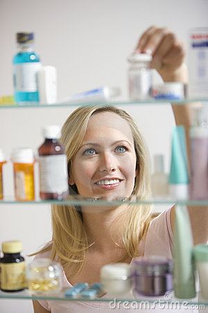 Free Woman Looking In Medicine Cabinet Stock Photography - 14646722