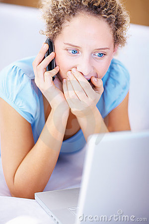 Woman looking at the laptop and getting surprised