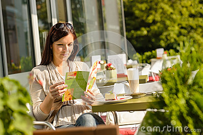 Woman looking at menu cafe bar terrace