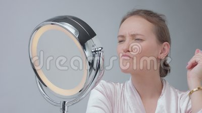 caucasian woman with mirror with ring light with no makeup
