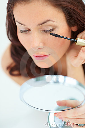 Woman looking into the mirror and using mascara