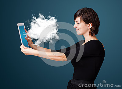 Woman looking at modern tablet with abstract cloud