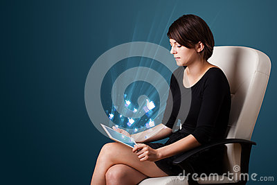 Woman looking at modern tablet with social icons