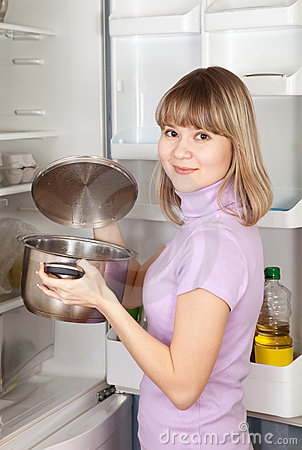 Woman looking into pan from  refrigerator
