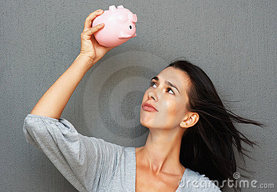 Woman looking at piggy bank suspiciously