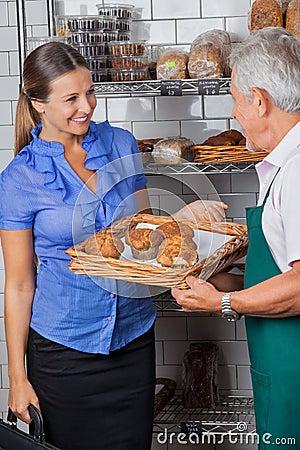 Woman Looking At Senior Salesman Holding Tray Of