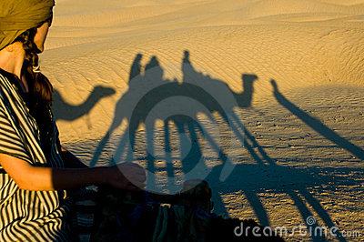 Woman looking at the shadows while camel riding