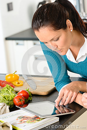 Woman looking tablet reading recipe kitchen vegetables