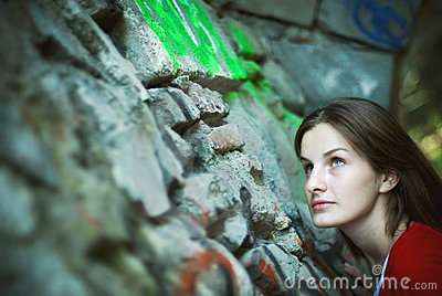 Woman looking up stone wall