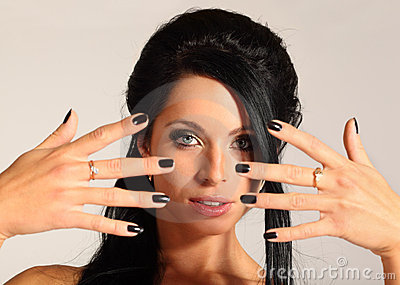 Woman looks through fingers, black manicure