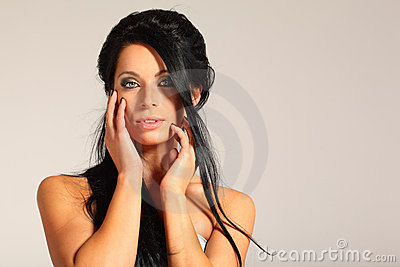 Woman looks inscrutable and touching her face