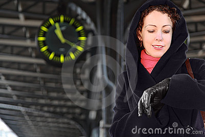 Woman looks at wristwatch, standing on station Stock Photo