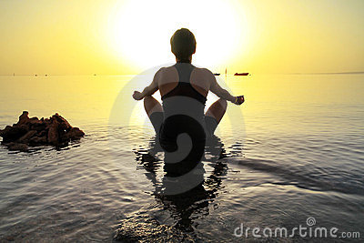 Woman in lotus pose at sunrise