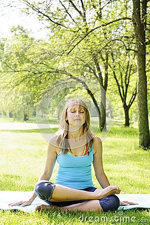 Woman in lotus yoga pose outside