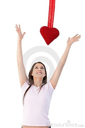 Woman in love trying to reach red heart smiling