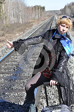 Woman with the luggage on the rails