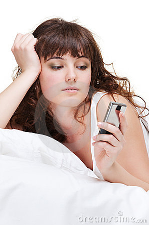 Woman lying in bed and looking at the phone