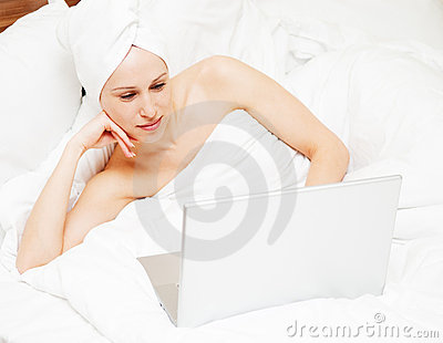 Woman lying on the bed and looking in to laptop
