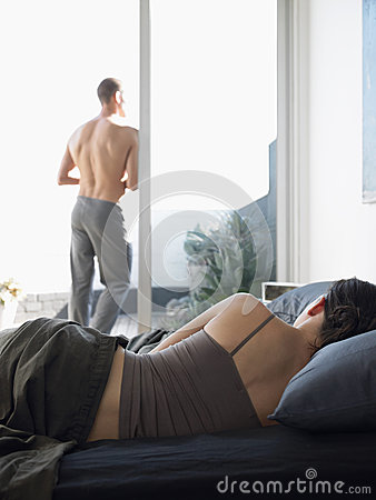 Woman Lying In Bed With Man Standing On Balcony