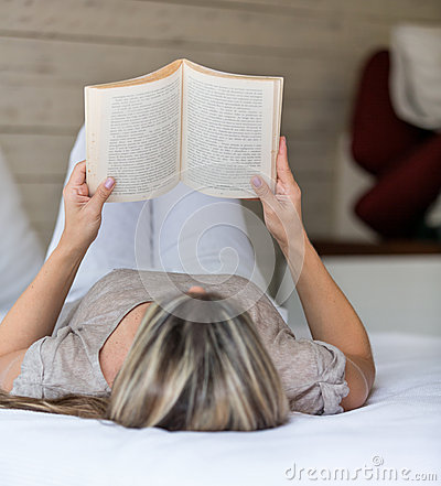 Woman lying in bed reading