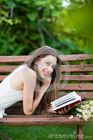 Woman lying on bench with book