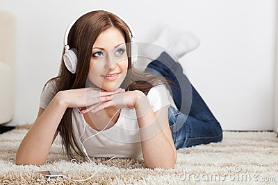 Woman lying on carpet and listen to the music