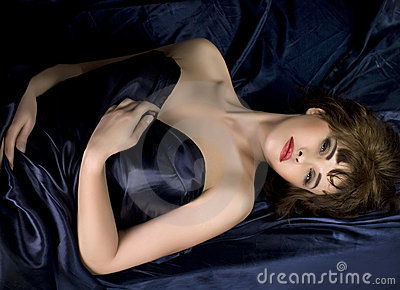 Woman lying on dark blue silk