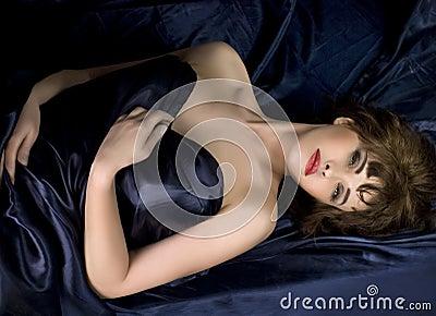 Woman lying on dark blue silk