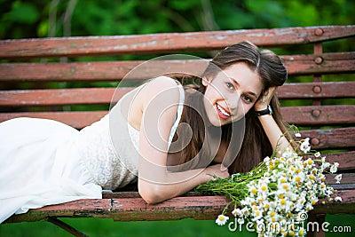 Woman lying down on bench