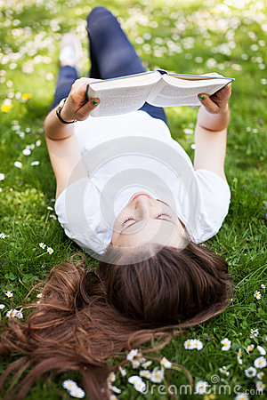 Woman lying down on grass with book