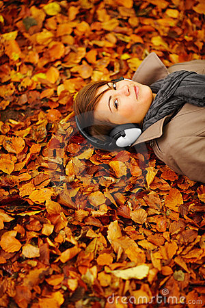 Woman lying down on leaves hearing music