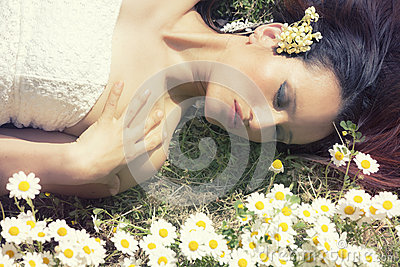 Woman lying on a grass flowers. Closed eyes. Horizontal Stock Photo