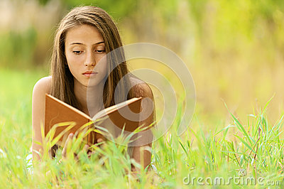 Woman lying on grass reading book