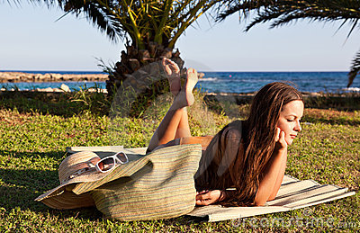 Woman is lying on green grass near the sea