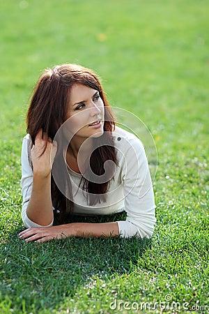 Woman lying on a green lawn