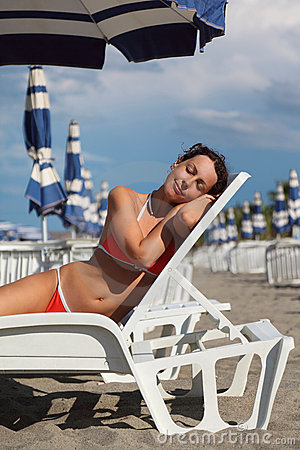 Woman lying on lounger under beach umbrella