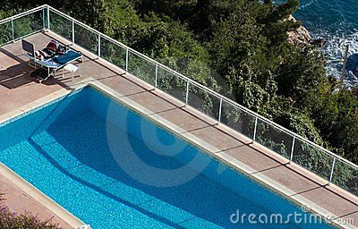 Woman Lying Next To A Pool In The Sun