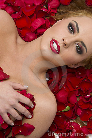 Stunning Woman lying red rose petals flowers
