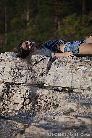 Woman lying upon rocks