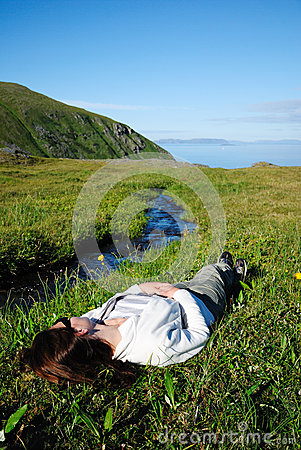 Woman lying supine near stream in green grass