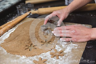 Woman makes christmas gingerbread cookies on black and red background Stock Photo