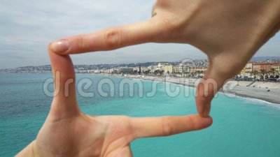 Woman makes a frame with fingers on the beach on the Cote d`azur Nice. Bay of angels Baie-des-Anges, Provence, France stock video